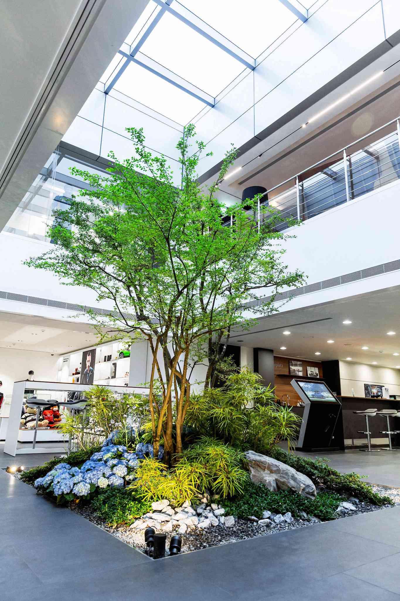 全新台北保時捷中心在室內打造天井融入一方綠意,將感性生活面巧妙隱身在科技理性面的環境中。