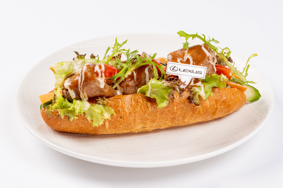 「法式燉牛肉堡」以法國長棍麵包搭配香嫩的菲力牛肉,沾上酸酸甜甜的蜂蜜芥茉醬,洋溢著美法交織的迷人風情 。