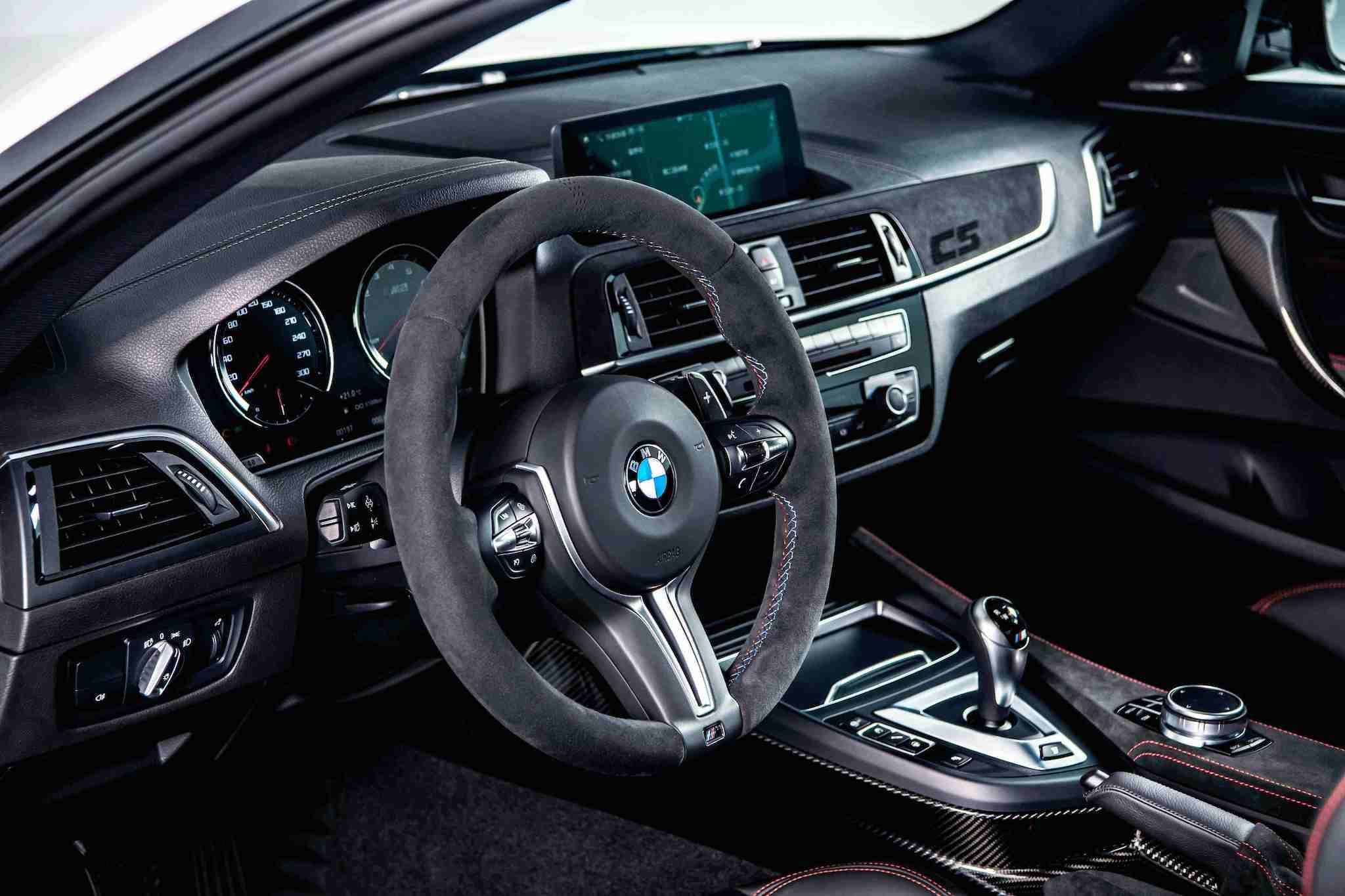全新 BMW M2 CS 處處可見 Alcantara 麂皮材質與對比紅色縫線設計,副駕駛座前方更鑲上專屬的紅色「CS」字樣。