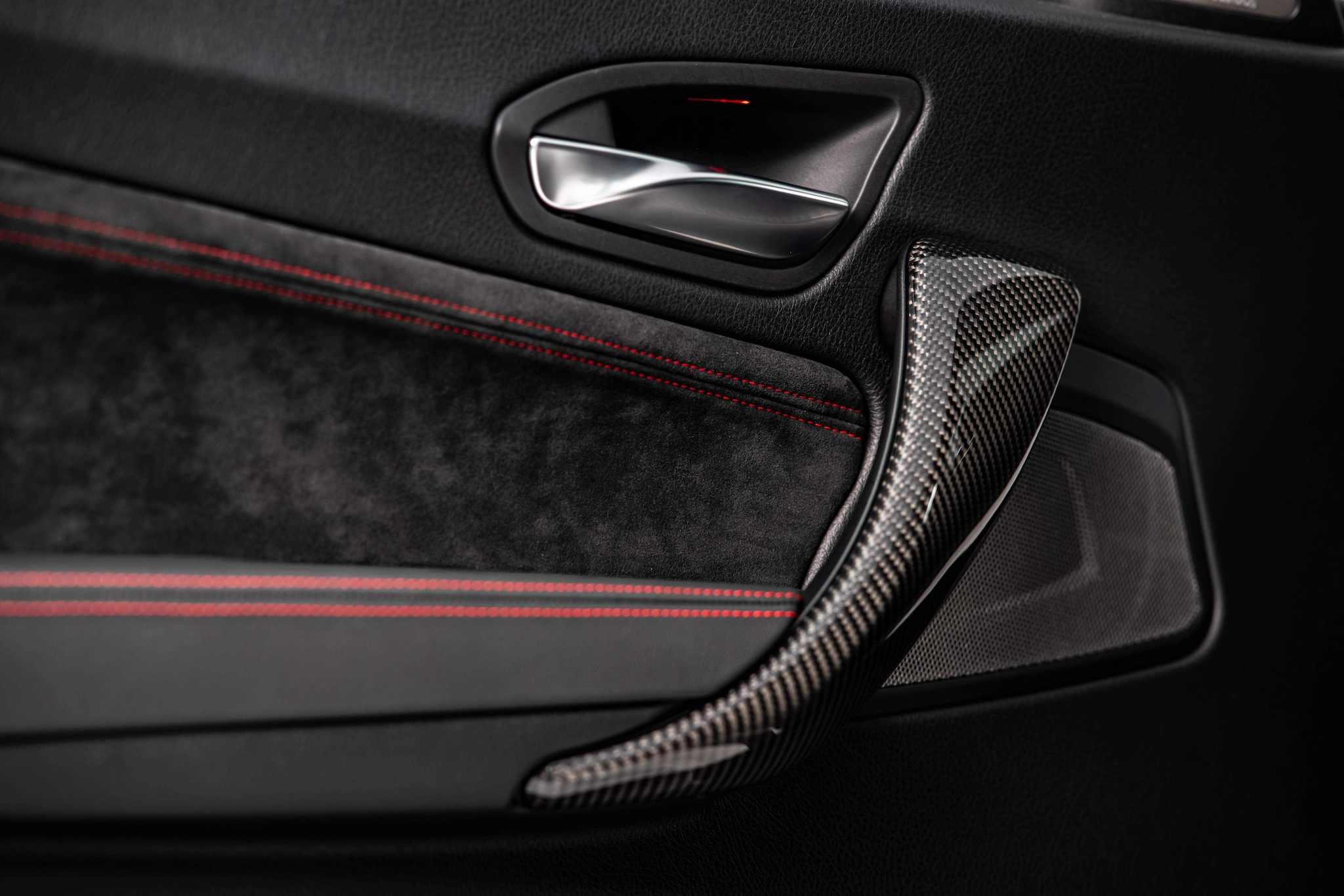 M2 CS 車內門板以柔軟麂皮包覆搭配碳纖維材質把手。
