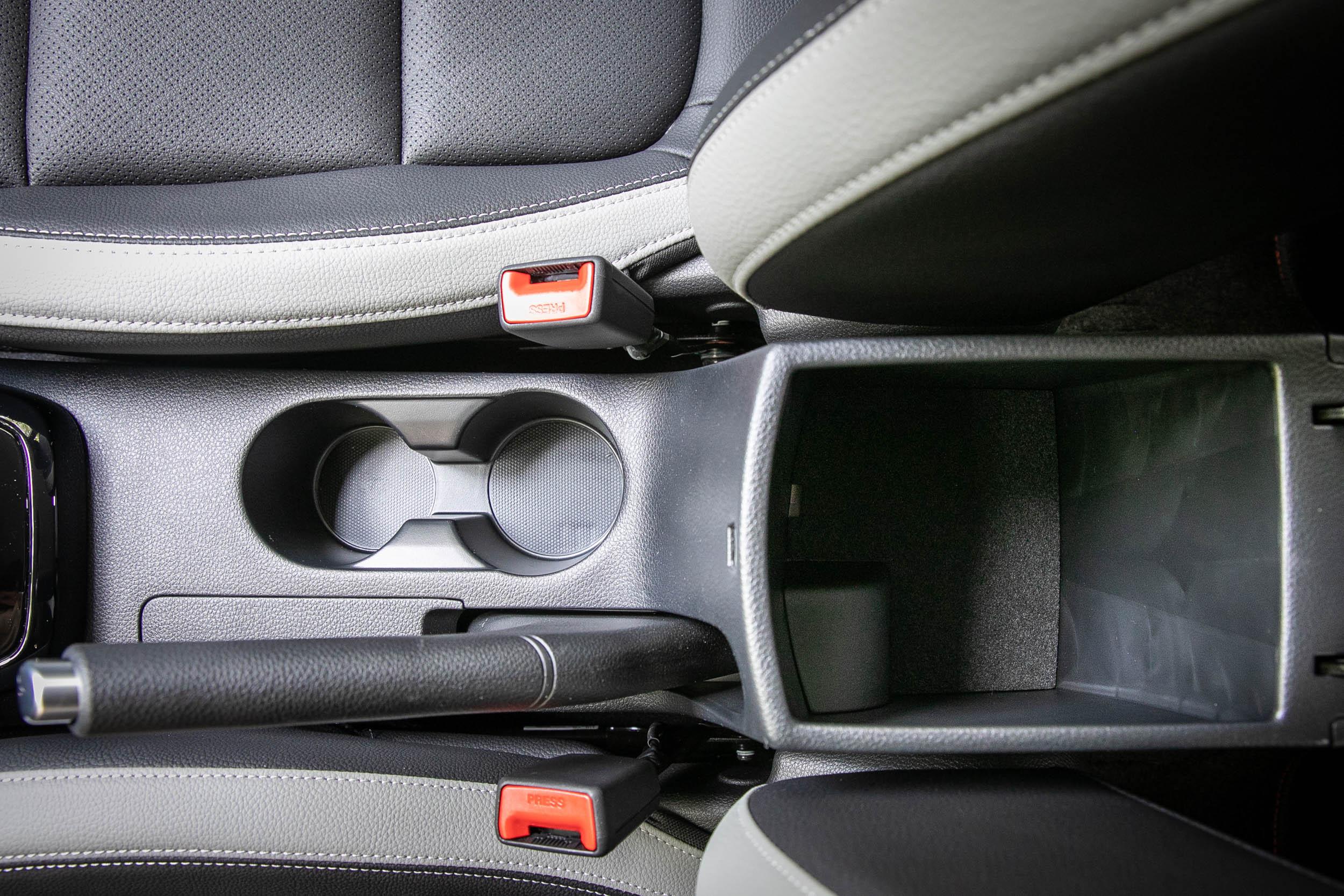 中央鞍座處的雙置杯架與中央扶手下挺深的置物空間。