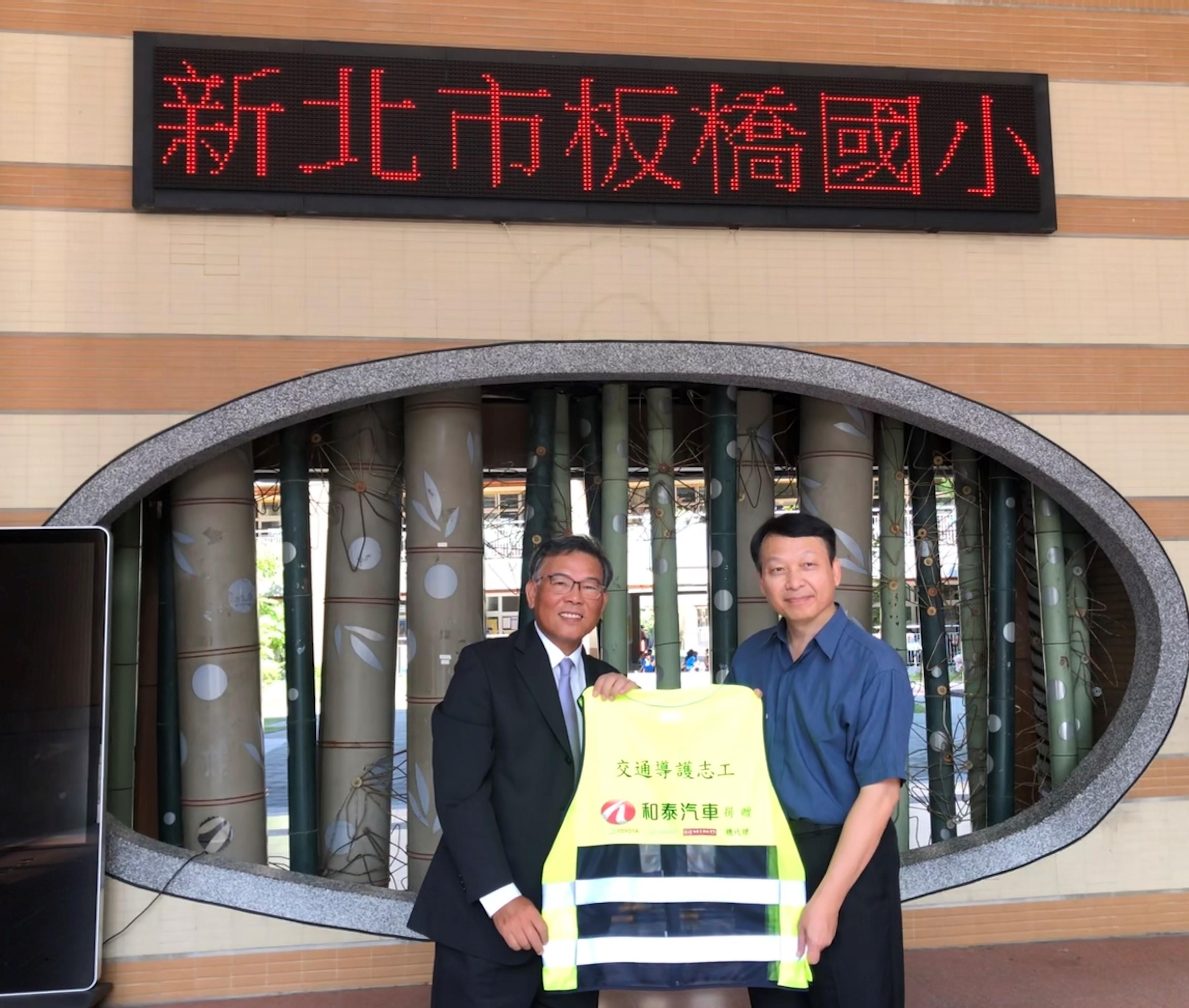 和泰汽車劉松山協理(左)捐贈導護裝備予板橋國小林義祥校長(右)。