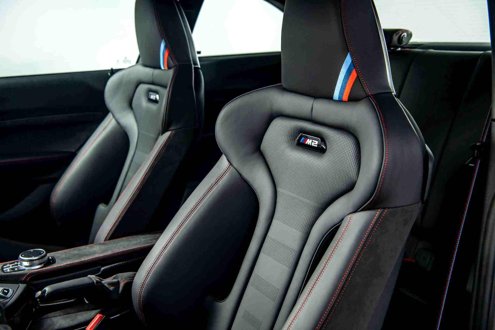 M2 CS 座椅使用與 M4 CS 相同的桶型 M 專屬跑車座椅,結合 Merino 真皮與Alcantara 麂皮雙材質;椅背上發光的 M2 銘牌與頭枕的經典 M 三色繡線裝飾。